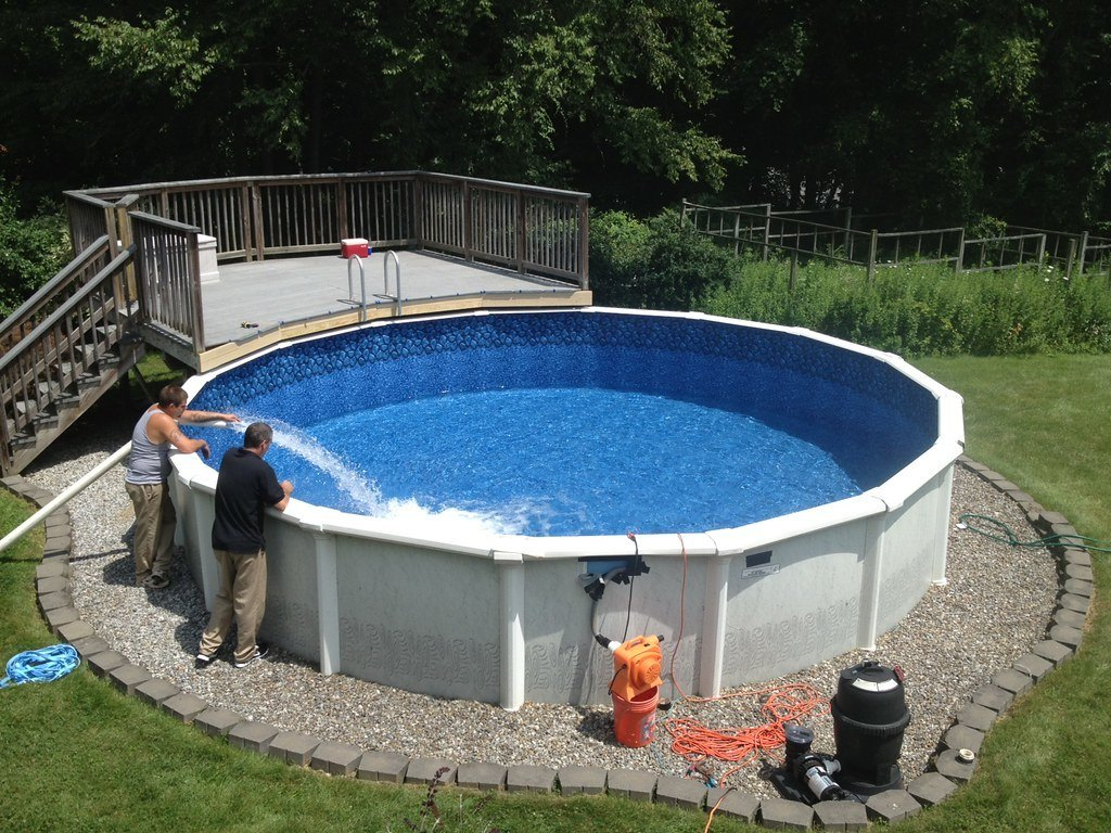 two people preparing the pool for swimming