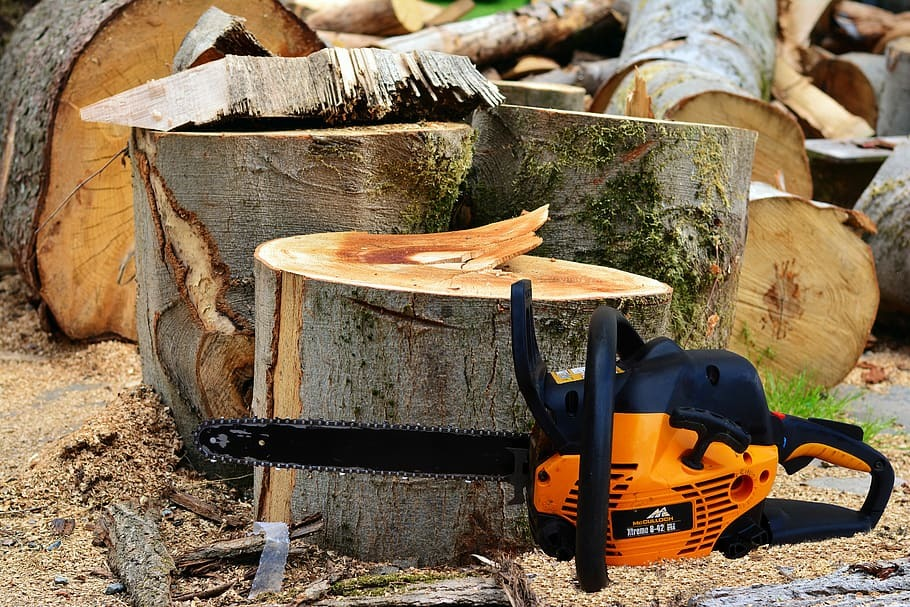 An orange chainsaw in front of the cut wood