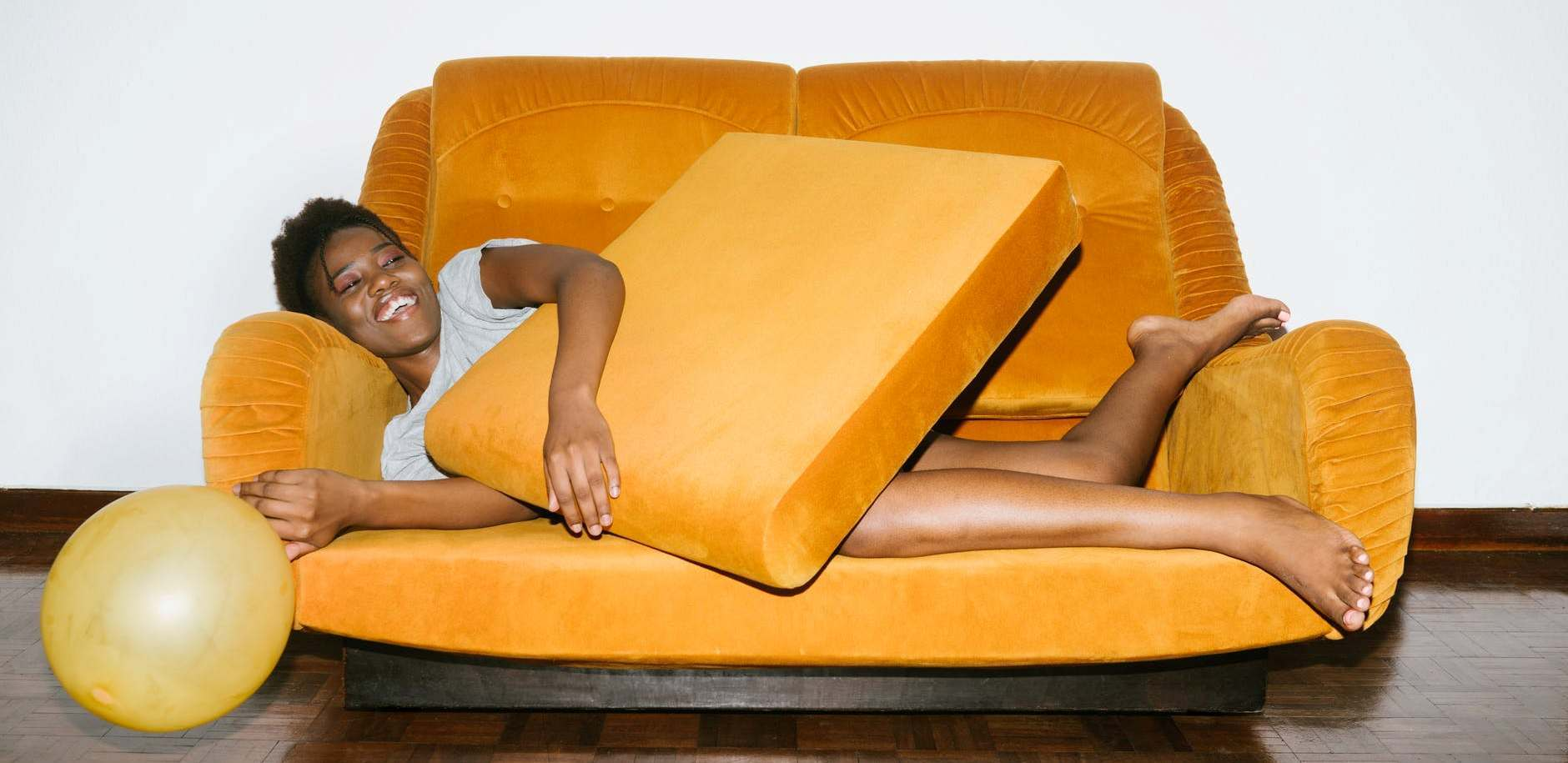 young woman laying on yellow couch